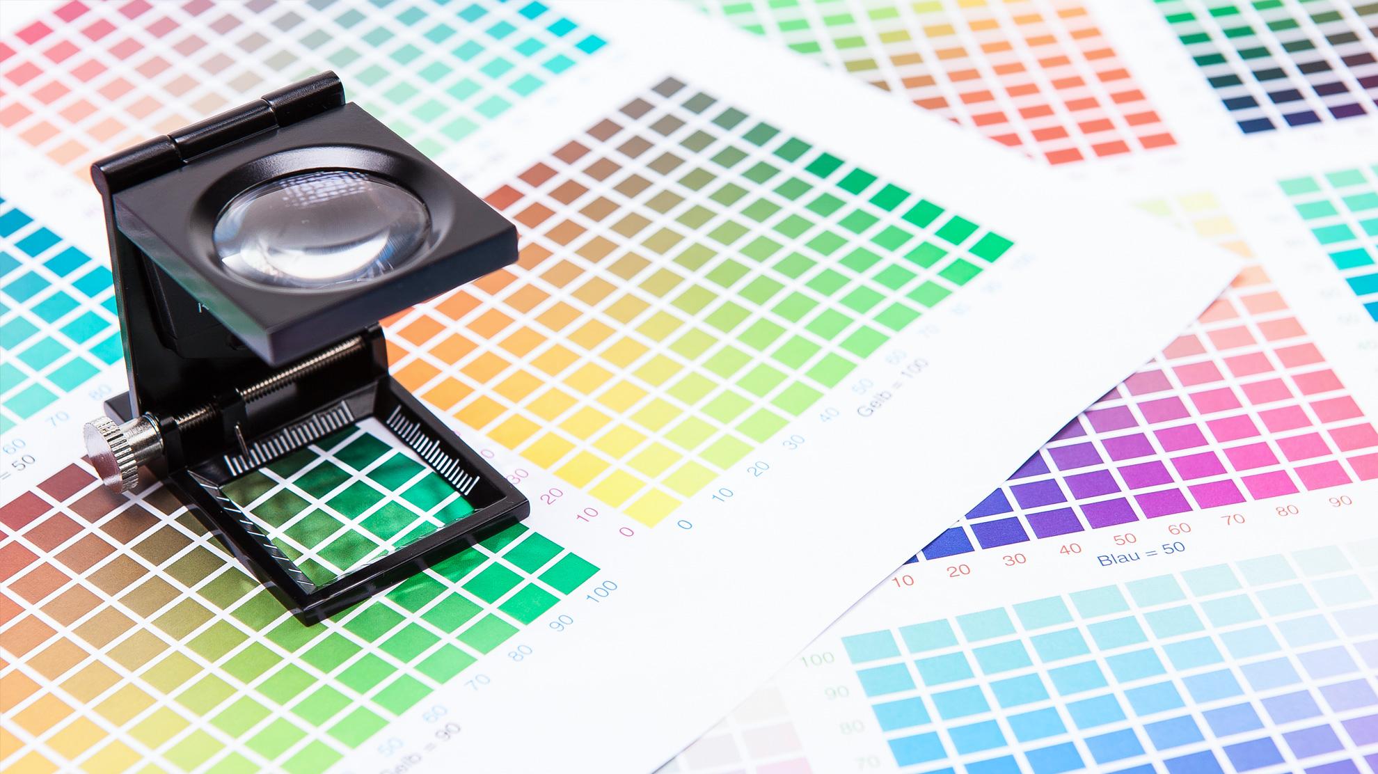 Druckproduktion: Eine Lupe liegt auf Farbmustern
