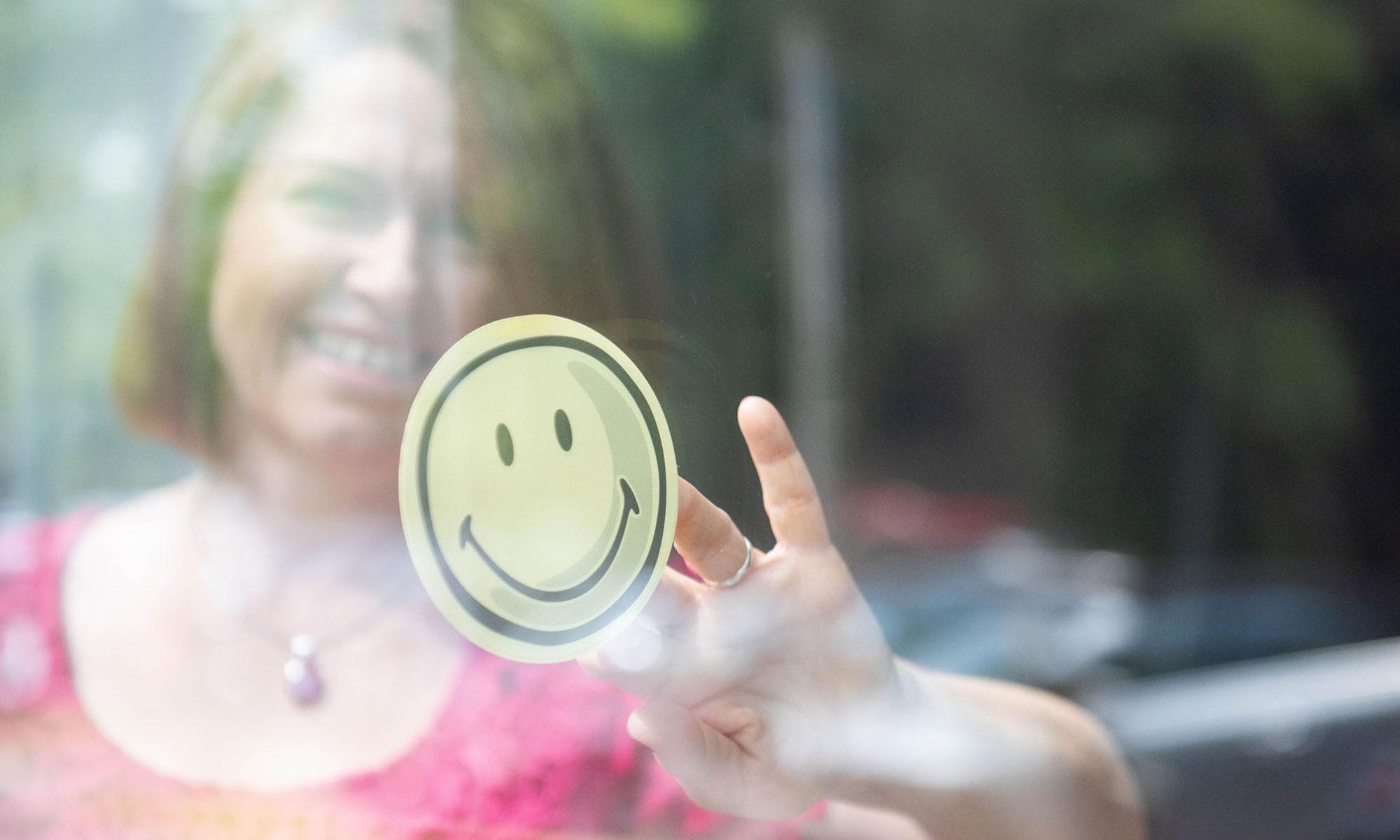 Sabine Valentin klebt einen Smiley auf die Scheibe